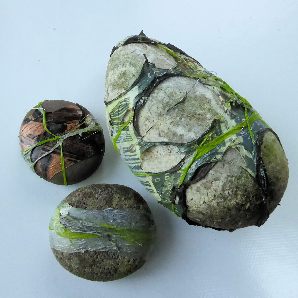 3 pebbles covered with plastic
