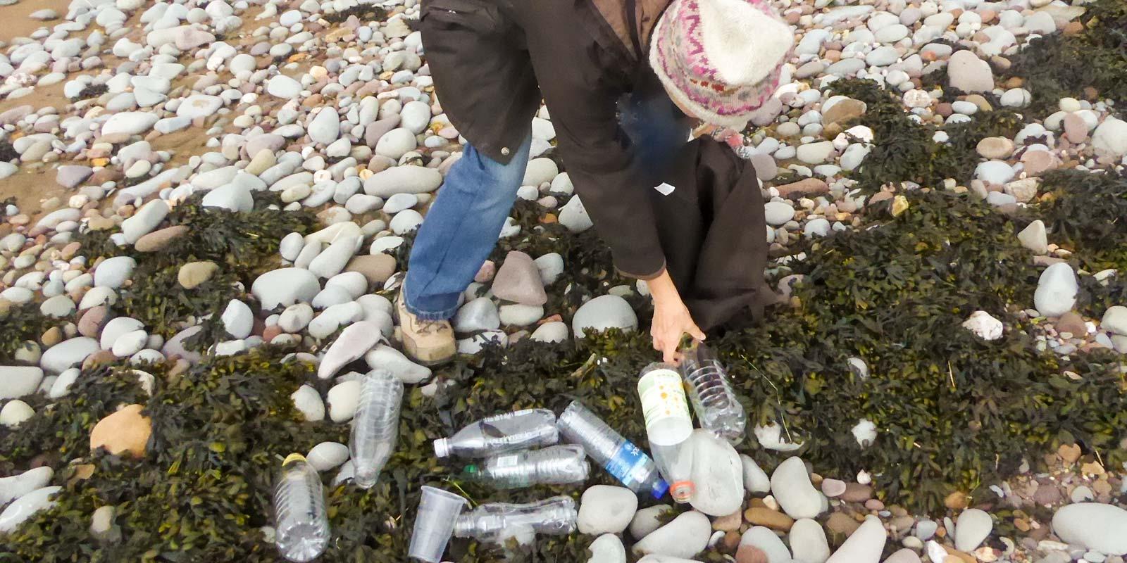 Siân Martin picking plastic bottles on a beach